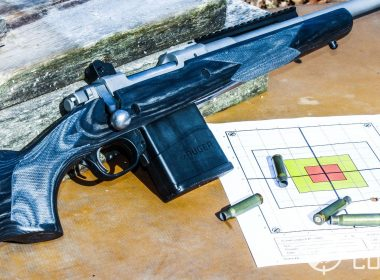 Close up of the excellent Ruger Scout Rifle shown with ammunition and targets.