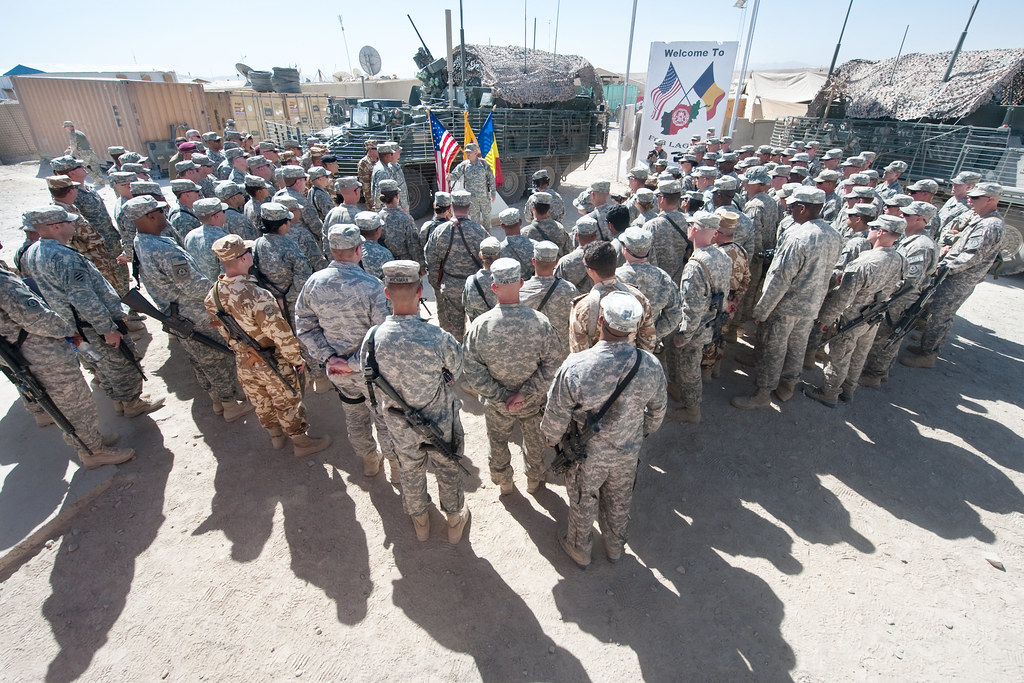 US and Romanian Soldiers huddle to listen to an address from the Chief of Staff of the US Army, Gen. George W. Casey Jr., at Camp Laughman, Afghanistan, Oct. 11, 2010.